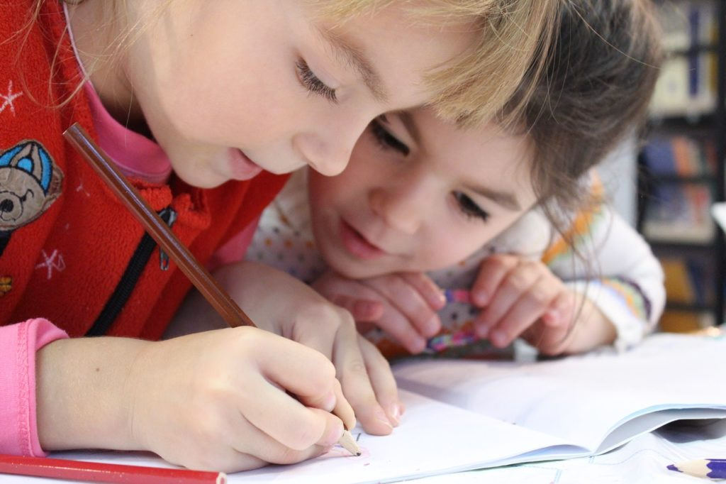 two kids drawing on paper